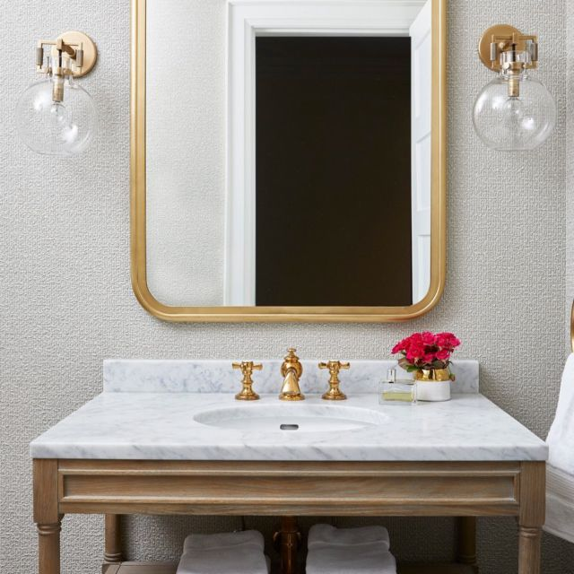 In order to amp up the sleekness of this powder room, we went for texturized wallpaper. It immediately added a subtle strength to the space.  The juxtaposition of the cooler marble countertop with the otherwise warm tones, including the gold accents, adds more intrigue. The square and rounded shapes also brought a playful balance.  . . . . . . #dvirainteriors #torontointeriors #powderroom  #torontodesigners #interiordesign #interiordesigner #bathroomlove #goldfaucet #interiordesigner #bathroomtrends #bathroomvibes #bathroomgoals #designtrends #kitchensofinstagram #luxurykitchens #dreamhome #dreaminteriors #bathroomideas #bathroomremodel #dreambathroom #bathroominspiration #bathroomreno #interiordesign