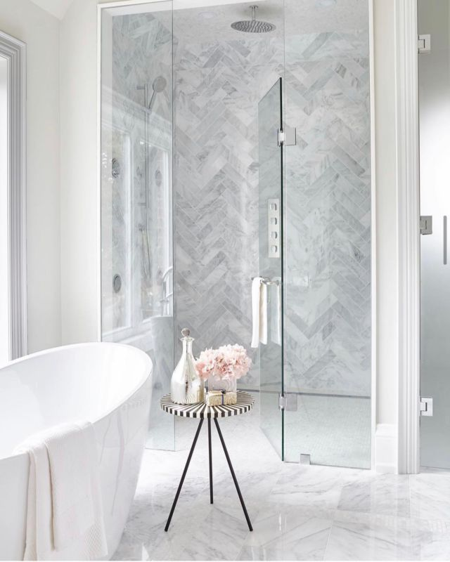 This spacious master bathroom feels bright with an all-white palette, accented with a sculptural bathtub and stylish checkerboard table.  My lovely clients wanted a bright and minimalist aesthetic for their master bathroom.   We achieved that feel in the space by using light and neutral marble tiles throughout the bathroom to evoke a spa like look.   We installed a frameless shower and steam room doors. And used neutral marble throughout and using different flooring for each space!  All these design elements created a bathroom that felt luxurious, brighter and bigger!  Bathrooms require a bit more design power when compared to larger spaces. There is so much to choose, from paint color to hardware, vanities and lighting, the list of factors to consider can be overwhelming.   Do you have a question about bathroom renovations? I'm always here to help! Contact us to book a design consultation. . . . . . .  #dvirainteriors #bathroomdesign #bathroomrenovation #luxuriousbathroom #luxurybathroom #spalikebathroom #spabathroom #bathroomescape #bathroomdecoration #bathroominterior #bathroominspiration #bathroominspo #bathroomgoals #bathroomtiles #bathroomstyle #bathroomtile #bathroomstyling #bathroomdesigns #dreambathroom#myhousebeautiful#homeinspo#homeideas#instadesign  #interiorinspo #inspiremeinterior #luxuryinteriors #worldofinteriors #luxeinteriors #bathroomvanity