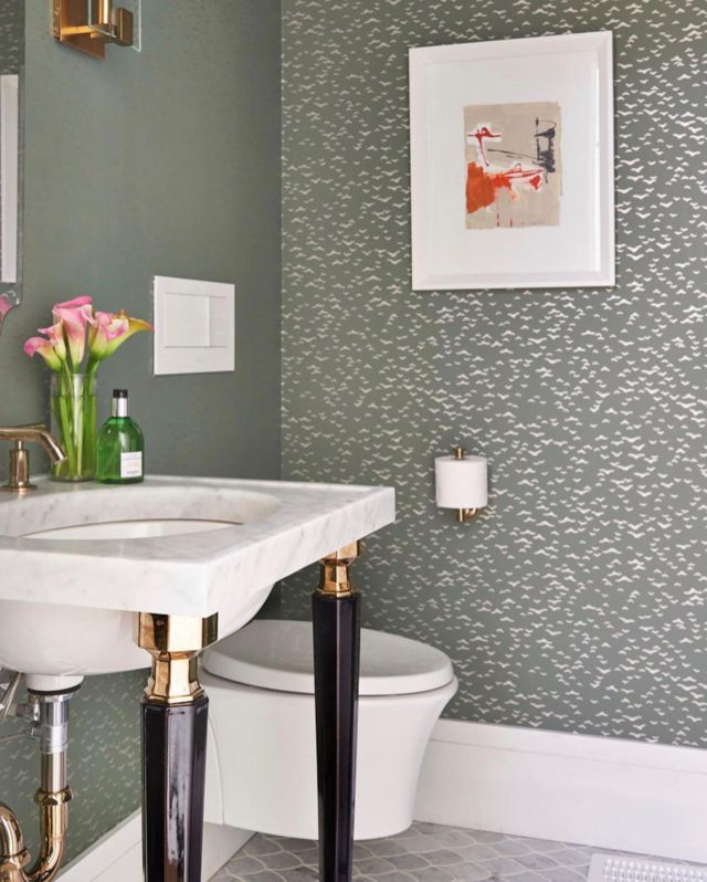 This spot-inspired wallpaper complements and contrasts nicely with the gold faucets and marble countertops. Those elements, along with the unique curved mirror, give this tiny bathroom a contemporary and more spirited spin.⠀⠀ ⠀⠀ If you could pick a wallpaper colour for your bathroom, what would it be? ⠀⠀ .⠀⠀ .⠀ .⠀ .⠀ .⠀ .⠀ ⠀ #interiorinspo #inspiremeinterior #luxuryinteriors #worldofinteriors #luxeinteriors #moderninteriordesign #interiorinstagram #cornerofmyhome #myhometrend #luxuryhouses ⠀ #customhomes #bedroomdecoration #bedroomdesigns #homedesignideas #homedesign #luxeathome #neutrals #momentsofchic #myhome2inspire #interiordecorating #littleflowers #projectmanagement #customhouse #luxuryfinishes  #bathroomremodel #houserenovation