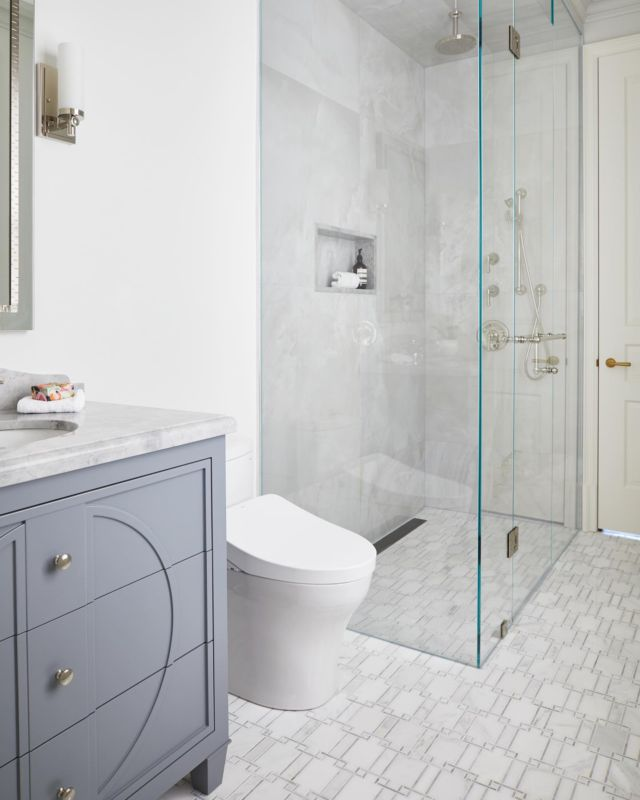 This bathroom makes a major—yet minimalist—statement.  The home owners love natural stone and wanted to introduce them in the kids bathrooms. What I love about working with stone is that the maintenance is low, the material is durable, and the look is captivating! The decision to install a glass panelled walk-in shower was intentional because it makes the space feel more luxurious than a skirted tub!⠀ ⠀⠀ We put a modern spin on this old world bathroom by using notable features, such as the glass-panelled walk-in shower and marble floor tiling throughout. We decorated the space with silver light hardware and faucets for a soft glittering, jewel-like effect!   Learn more about project Napier on our website 👇 www.dvira.com/galleries/napier  Are you looking to create your dream home? Ensure the careful smart planning you need from day one, and contact Dvira Interiors!   We look forward to incorporating our vision, scope, technical expertise, and industry connections to make your home's design/build experience as positive and rewarding as possible.  www.dvira.com . . . . . . . . .⠀ .⠀ .⠀ #dvirainteriors #torontodesigner #bathroomsofinsta  #bathroomgoals #bathroomideas #interiordesign #luxuryfinishes #interiordesigner #contemporaryinteriors #oldmeetsnew #silverdetails #silverfaucet #glasspanelledshower #kleinburg #whitevanity #bathroomhardware #bathroomstorage #skirtedtub #masterbathroom #bathroomdesign #bathroomdesign  #whitetile #whitetilelayout #oldworld #oldworlddesign #powderroom #luxurydesign #luxurybathrooms #bathroomstyle #bathroomdesign